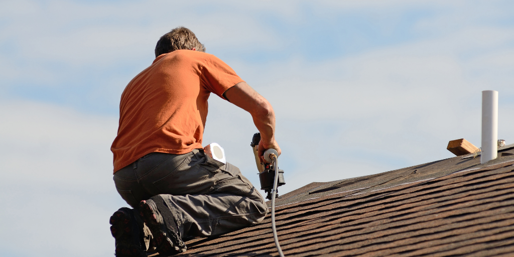 A white male in an orange t-shirt on top of a roof demonstrating how to perform a roofing contractor task.